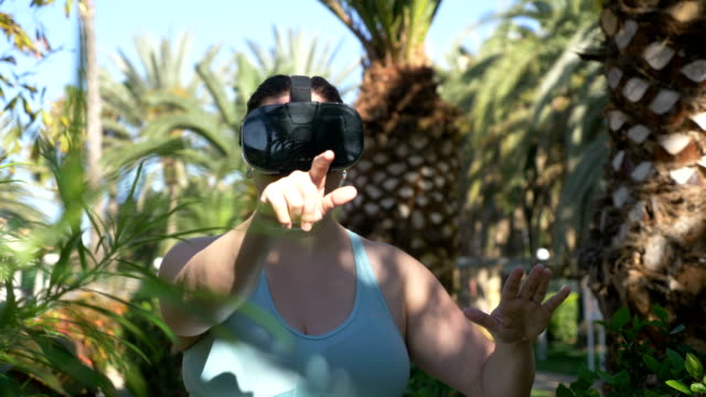 Video-of-woman-exploring-virtual-reality-in-tropical-resort-in-4k
