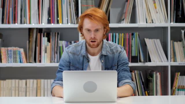 Hombre-sorprendido-aturdido-con-pelos-rojos-trabajando-en-ordenador-portátil