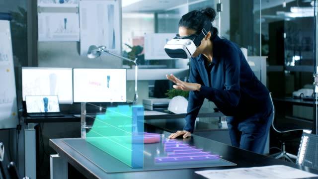 En-la-mujer-profesional-de-oficina-llevando-casco-de-realidad-aumentada-interactúa-con-infografías-que-muestran-las-estadísticas-Ella-se-inclina-sobre-la-mesa-con-animación-3D-crecimiento-de-la-empresa-mostrando-modelos-