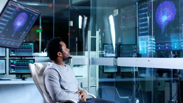 En-el-hombre-de-laboratorio-neurológico-en-una-silla-mira-representación-de-exploración-del-cerebro-y-salud-infografía-se-muestra-en-los-monitores-