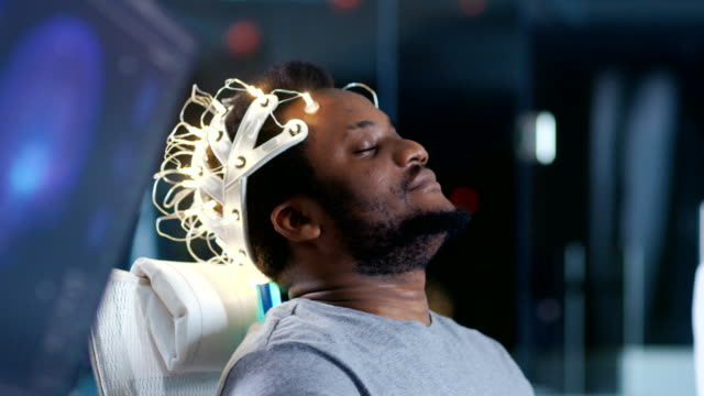 In-Laboratory-Man-Wearing-Brainwave-Scanning-Headset-Sits-in-a-Chair-with-Closed-Eyes-Monitors-Show-EEG-Reading-and-Graphical-Brain-Model-In-the-Modern-Brain-Study/-Neurological-Research-Laboratory-