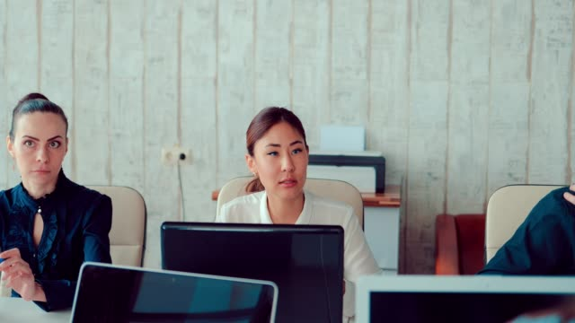 Asian-girl-behind-laptops-in-the-office-communicates-with-colleagues-they-team-discuss-business-ideas