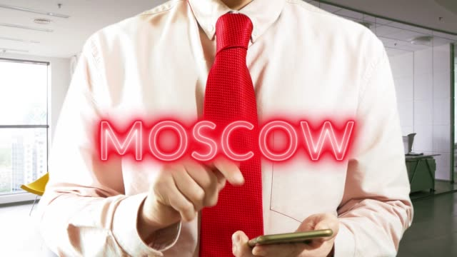 Moscow-Businessman-chooses-а-city-on-virtual-interface-in-light-office-Concept:-business-trip-hologram-technology-augmented-reality-future-travel