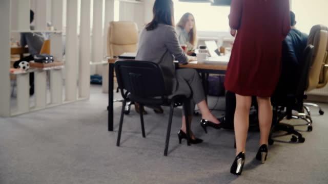 Gente-de-negocios-multiétnico-feliz-reunión-Secretaria-mujer-entra-en-la-oficina-da-documentos-a-Jefe-femenino-europeo-4K
