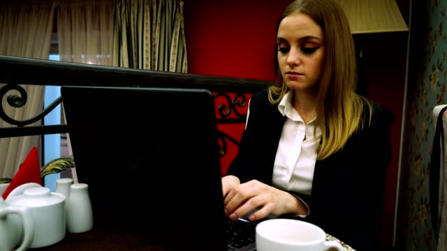 The-businesswoman-sits-on-the-couch-and-typing-the-text-on-the-laptop