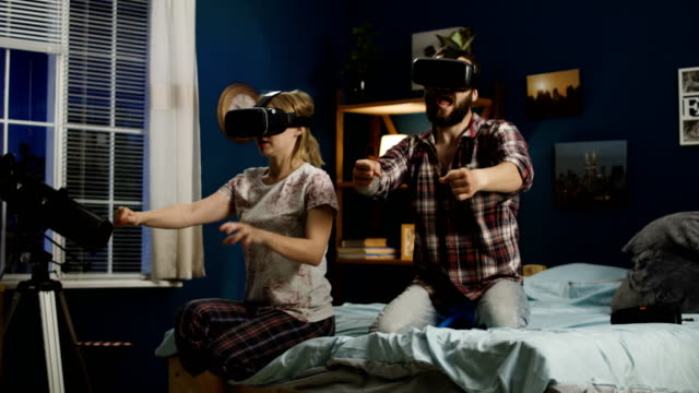 Couple-in-VR-glasses-having-fun-on-bed