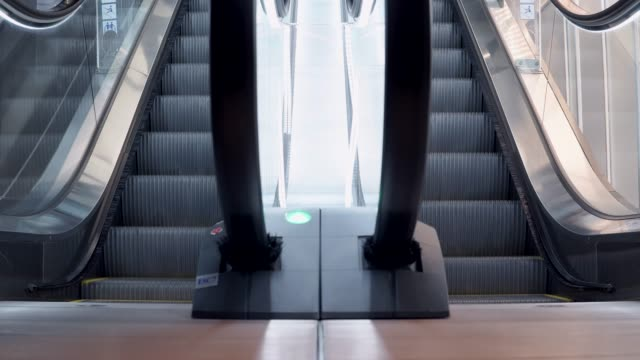 Young-man-walking-up-on-modern-escalator-stairs-Moving-staircase-running-up-and-down-urban-lifestyle-concept-