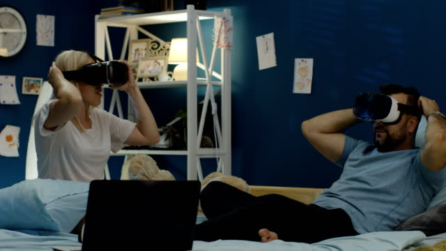 Couple-in-VR-glasses-chilling-on-bed