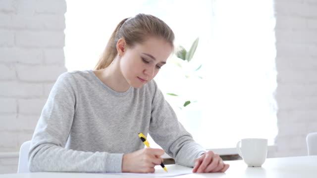 Mujer-joven-escribir-documentos-en-la-oficina-papeleo