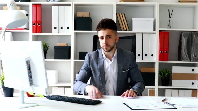 director-in-gray-jacket-sitting-at-table-in-white-office-and-shaking-head-negatively
