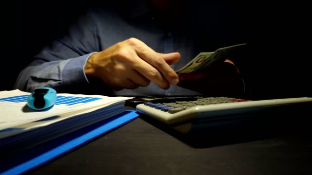 Man-is-counting-dollar-banknotes-and-using-calculator-Loans-in-the-office-