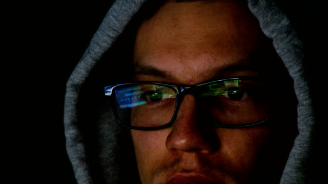 Hacker-in-glasses-and-a-hood-works-behind-a-computer-in-the-dark-the-program-code-is-reflected-in-glasses-close-up-4k