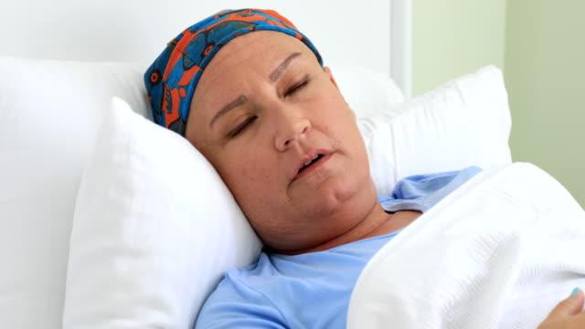 Mujer-de-media-edad-con-cáncer-tendido-en-una-cama