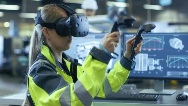Weibliche-Wirtschaftsingenieur-tragen-virtuelle-Realität-Kopfhörer-und-Holding-Controller-sie-nutzt-VR-Technologie-für-Industrie-Design-Entwicklung-und-Prototyping-in-CAD-Software-