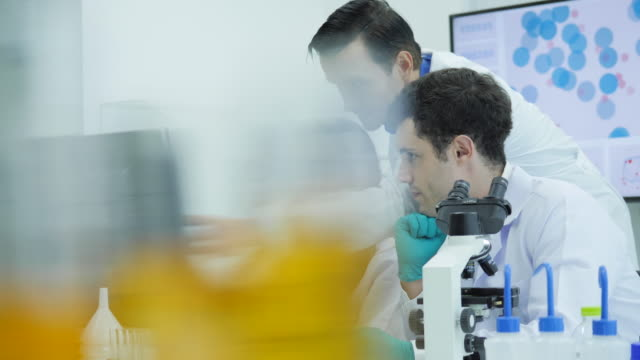 Team-of-medical-research-scientists-are-working-on-computers-and-having-a-meeting-in-the-modern-laboratory