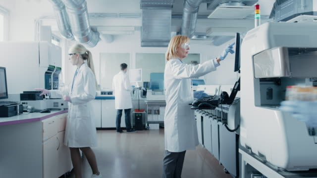 Team-of-Research-Scientists-Working-On-Computer-with-Medical-Equipment-Analyzing-Blood-and-Genetic-Material-Samples-with-Special-Machines-in-the-Modern-Laboratory-
