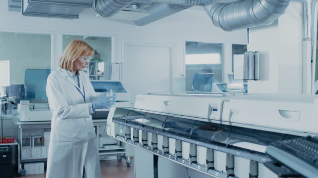 In-Laboratory-Female-Scientist-Takes-Out-Test-Tube-with-Blood-Samples-Out-of-the-Medical-Equipment-and-Analyzes-Data-with-Personal-Computer-Team-of-Researchers-Work-in-Pharmaceutical-Laboratory-