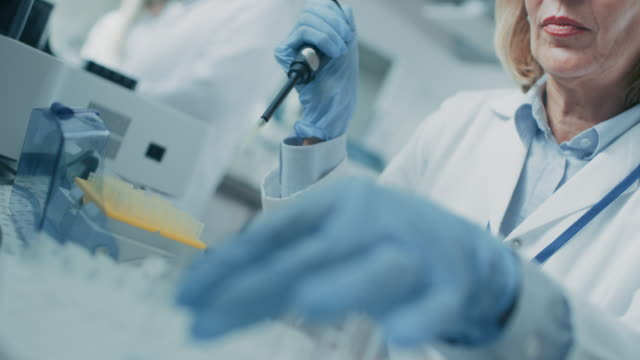 Close-up-of-the-Hand-in-Glove-Using-Micro-Pipette-while-Working-with-Test-Tubes-People-in-Innovative-Pharmaceutical-Laboratory-with-Modern-Medical-Equipment-for-Genetics-Research-