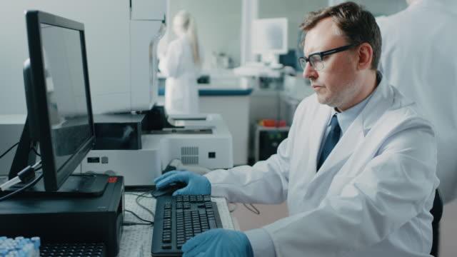 Investigador-masculino-se-sienta-en-su-lugar-de-trabajo-en-laboratorio-utiliza-equipo-Personal-Que-la-genética-de-fondo-centro-de-investigación-farmacéutica-con-equipos-innovadores-