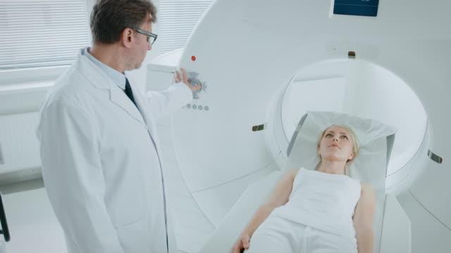 Im-medizinischen-Labor-kontrolliert-männlichen-Radiologe-MRT-oder-CT-oder-PET-Scan-mit-weiblichen-Patienten-unterziehen-Verfahren-High-Tech-moderne-Medizintechnik-Erhöhte-Kameraeinstellung-