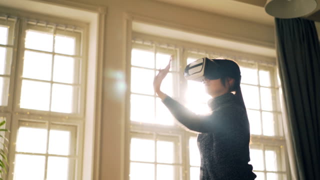 Laughing-young-girl-in-sweater-is-having-fun-with-virtual-reality-glasses-moving-hands-standing-in-light-studio-with-goggles-on-her-head-and-enjoying-gadget-