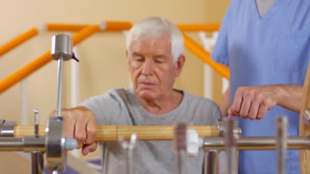 Senior-hombre-usando-ejercitador-de-muñeca-en-período-de-sesiones-de-fisioterapia