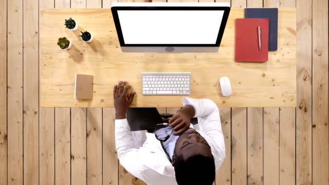African-doctor-watching-something-on-the-screen-of-computer-White-Display