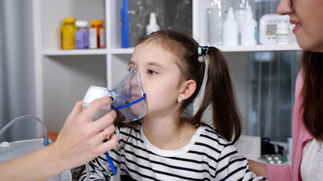 Portrait-of-a-woman-pediatrician-and-a-little-girl-with-an-inhalation-mask-from-a-nebulizer-in-the-hospital-