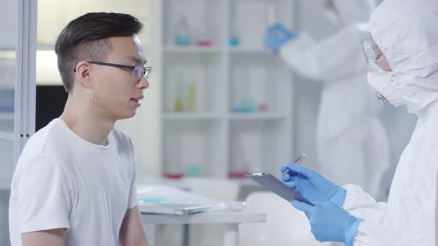 Hombre-infectado-describiendo-síntomas-al-médico-en-cubiertas-desechables