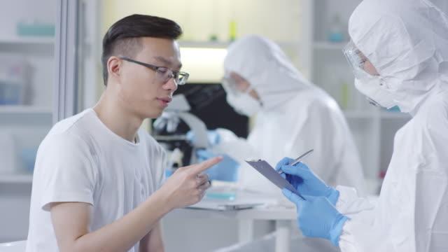 Asian-Man-Describing-Symptoms-to-Doctor-in-Disposable-Coveralls