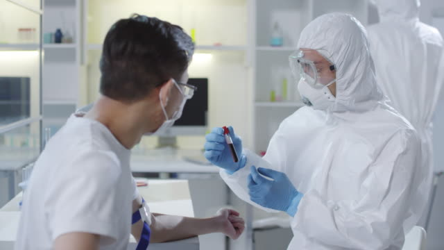 Doctor-in-Protective-Gear-Showing-Blood-Sample-to-Patient