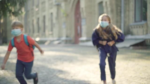 Estudiantes-de-secundaria-con-máscaras-faciales-divirtiéndose-en-el-patio-de-la-escuela-en-el-día-soleado-Retrato-de-alumnos-caucásicos-positivos-relajados-huyendo-Niños-disfrutando-del-ocio-después-de-estudiar-pandemia-de-Covid-19-