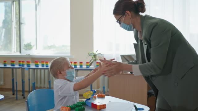 niño-lindo-enmascarado-con-síndrome-de-down-jugando-pat-a-cake-con-su-profesor-sentado-en-el-escritorio-ocio-en-la-escuela-después-del-encierro