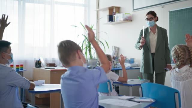 después-de-la-vida-de-cuarentena-el-maestro-enmascarado-muestra-a-los-alumnos-tarjetas-con-cartas-los-niños-levantan-la-mano-sabiendo-la-respuesta-correcta-sentado-en-los-escritorios-en-el-aula