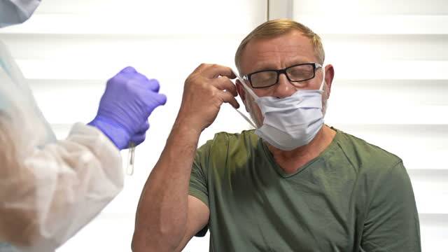 Lab-technician-in-a-protective-suit-takes-a-swab-from-an-elderly-patient-for-coronavirus