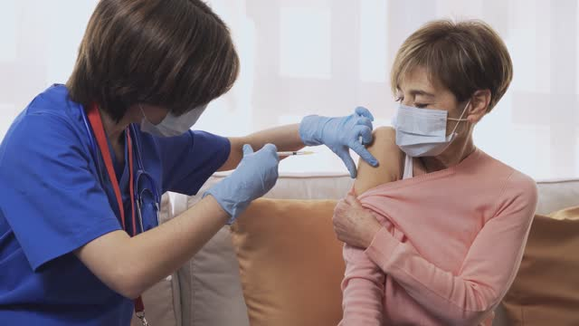 Nurse-giving-coronavirus-vaccine-to-senior-woman-inside-home-during-lockdown-isolation---Covid-19-injection-to-patient-concept---Focus-on-hand
