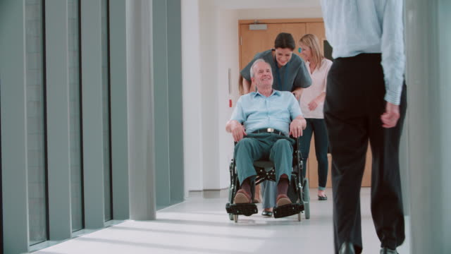 Nurse-Pushing-Senior-Patient-In-Wheelchair-Along-Corridor