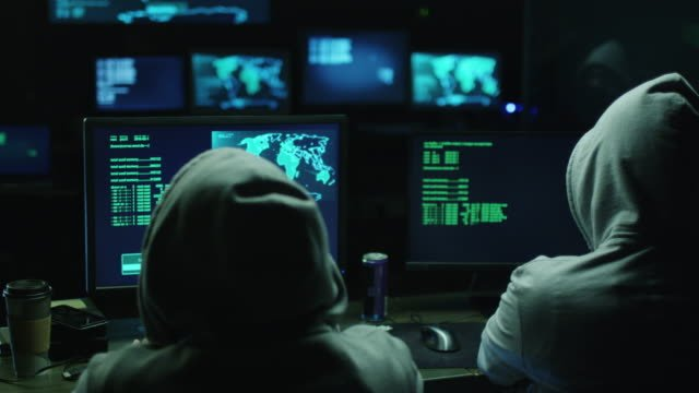 Two-hackers-in-hoods-work-on-a-computers-with-maps-and-data-on-display-screens-in-a-dark-office-room-