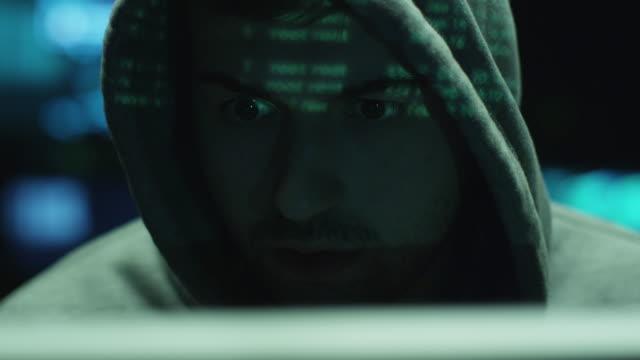 Macho-hacker-trabajando-con-una-computadora-mientras-verde-código-caracteres-reflexionar-sobre-su-rostro-de-oficina-en-una-sala-oscura-
