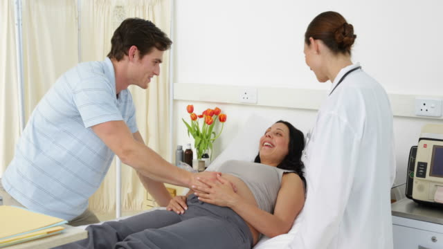 Pregnant-woman-lying-on-bed-talking-with-partner-and-doctor