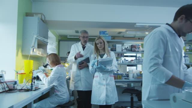 Los-científicos-Senior-y-femeninos-con-papeles-y-tabletas-caminan-y-tienen-una-conversación-en-un-laboratorio-