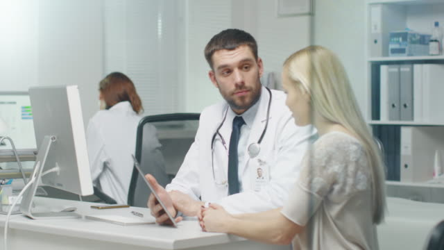 In-Doctor-s-Office-Professional-Doctor-Consults-Beautiful-Young-Woman-with-a-Help-of-a-Tablet-They-Look-and-the-Screen-and-Smile-