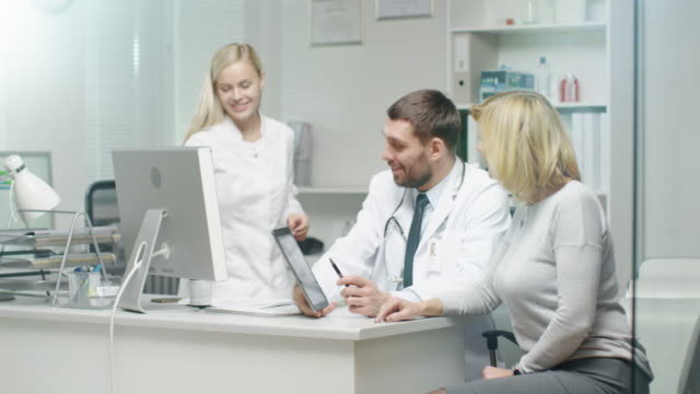 Professional-Doctor-Consults-Mid-Adult-Woman-He-Points-out-Something-on-the-Screen-to-Her-Nurse-Puts-Documents-on-Doctor-s-Table-
