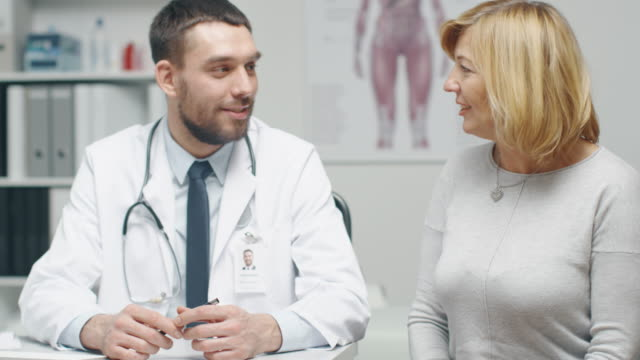 Male-Doctor-Consults-Mid-Adult-Female-Patient-They-Talk-and-Smile-