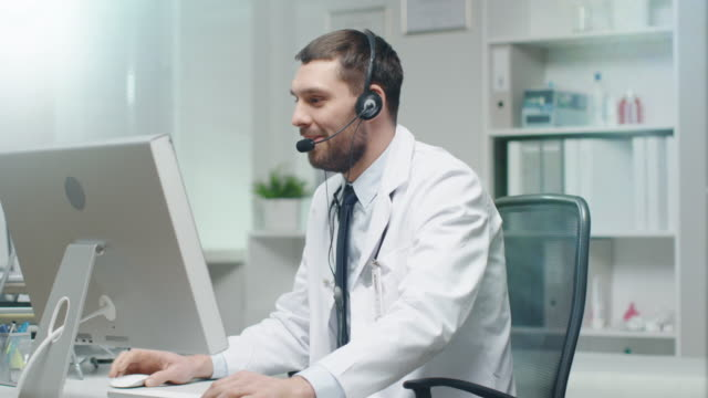 Male-Doctor-Consults-Patients-on-the-Internet-He-Sits-before-His-Personal-Computer-and-Wears-Microphone-