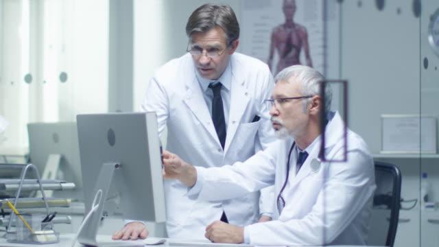 Doctor-Senior-y-su-asistente-discuten-el-registro-del-paciente-en-el-ordenador-personal-En-slow-motion-