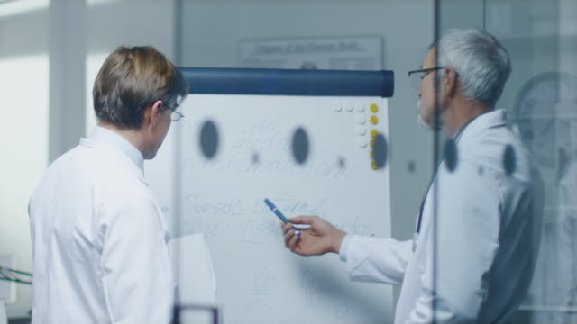 Two-Specialist-Doctors-Discussing-Health-Issues-and-Medical-Drug-Trial-Results-over-Whiteboard-