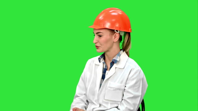 Female-engineer-in-safety-helmet-sitting-and-talking-on-a-Green-Screen-Chroma-Key