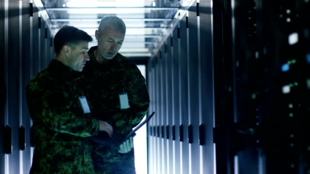 In-Data-Center-Two-Military-Men-Work-with-Open-Server-Rack-Cabinet-One-Holds-Military-Edition-Laptop-