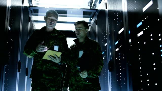 Dos-soldados-caminando-en-el-corredor-del-centro-de-datos-Uno-sostiene-Tablet-PC-tienen-discusión-Filas-de-servidores-de-datos-de-trabajo-por-sus-lados-